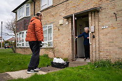 Tony Rosa delivers food packages from Enfield Council to Marim Surridge in Enfield, north London.