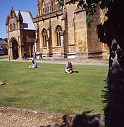 A3AAH2 People sitting on grass lawn Sherborne Abbey church Dorset England