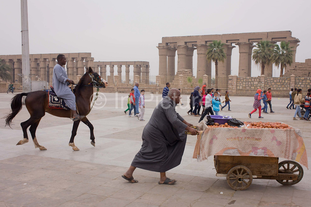 A mounted horse and tourist stallholder in front of the ancient Egyptian columns of Luxor Temple, Luxor, Nile Valley, Egypt. Local businesses are obviously very dependent of the tourism industry and therefore badly affected by the downturn. According to the country's Ministry of Tourism, European visitors to Egypt is down by up to 80% in 2016 from the suspension of flights after the downing of the Russian airliner in Oct 2015. The temple behind was built by Amenhotep III, completed by Tutankhamun then added to by Rameses II. Towards the rear is a granite shrine dedicated to Alexander the Great and in another part, was a Roman encampment. The temple has been in almost continuous use as a place of worship right up to the present day.