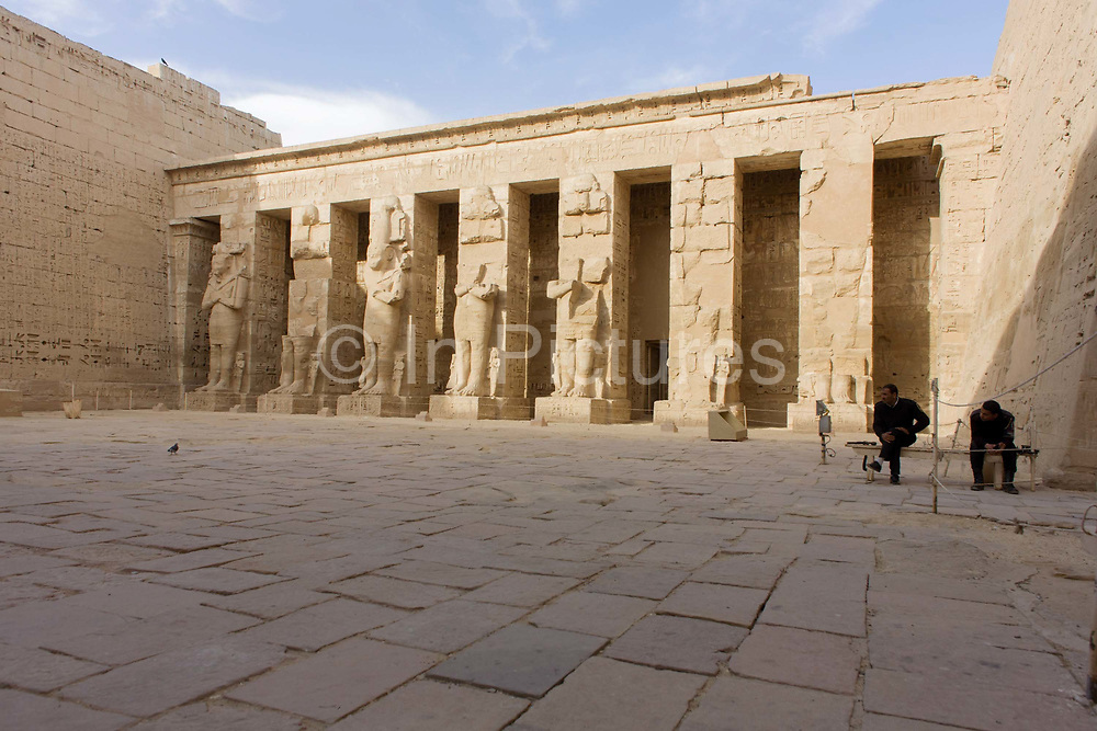 Guards await tourists near Ramessid columns in the peristyle court at the ancient Egyptian site of Medinet Habu (1194-1163BC), the Mortuary Temple of Ramesses III in Luxor, Nile Valley, Egypt. Medinet Habu is an important New Kingdom period structure in the West Bank of Luxor in Egypt. Aside from its size and architectural and artistic importance, the temple is probably best known as the source of inscribed reliefs depicting the advent and defeat of the Sea Peoples during the reign of Ramesses III. According to the country's Ministry of Tourism, European visitors to Egypt is down by up to 80% in 2016 from the suspension of flights after the downing of the Russian airliner in Oct 2015. Euro-tourism accounts for 27% of the total flow and in total, tourism accounts for 11.3% of Egypt's GDP.