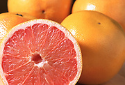 Close up selective focus photograph of a group of Pink Grapefruits with one cut open