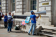 A man takes a photograph of  Anti Brexit campaigner Steve Bray protesting outside the Cabinet office in Whitehall as Ministers hold a Brexit Cabinet meeting on 19th August 2019 in London, United Kingdom.