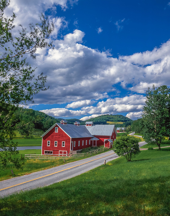 Red barns complex nestled between country road & river, summer, Pomfret, VT