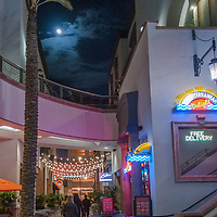 Shoppers enjoy Christmas lights & the moon under a palm tree in a mall in Glendale, California.