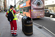 Worker disinfects the areas which people regulalrly touch with their hands along Oxford Street as a bus with a giant human eye passes, with the Coronavirus lockdown measures are set to ease further, the west end starts to fill with people as they return to the shopping district and the quiet city starts coming to an end on 22nd June 2020 in London, England, United Kingdom. As of today the government has relaxed its lockdown rules, and is allowing some non-essential shops to open with individual shops setting up social distancing queueing systems.