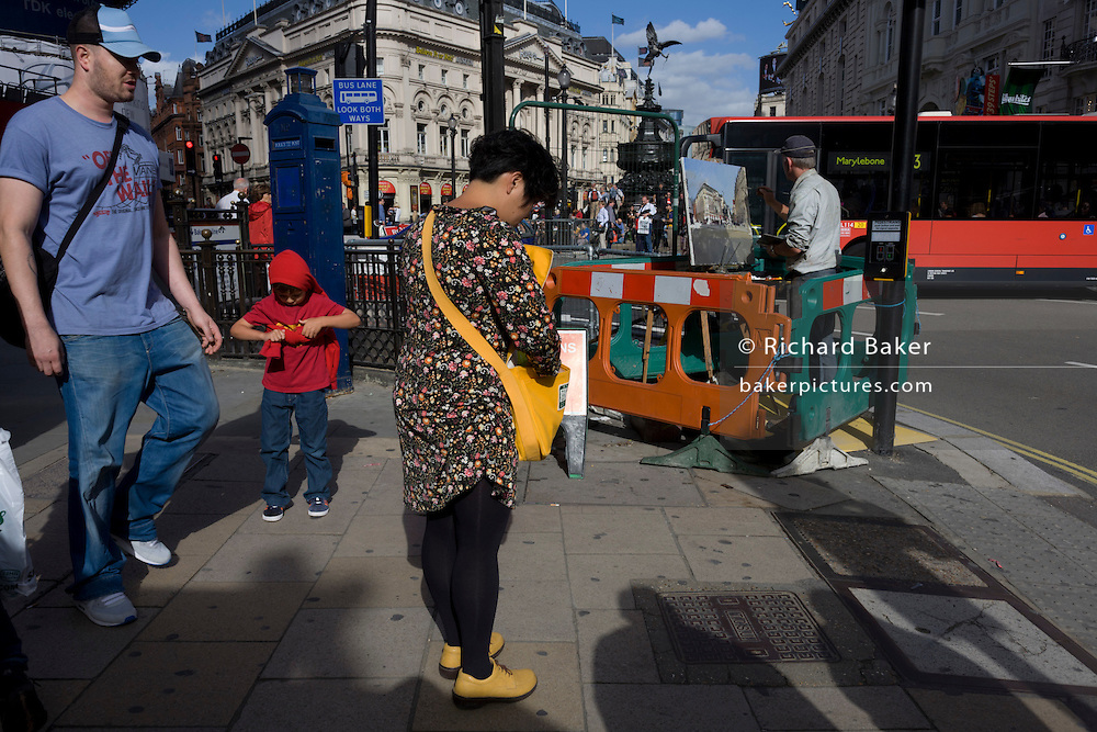 An artist is enclosed in roadworks barriers at the busy junction of Piccadilly Circus in London's West End.