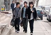 Chinese teenagers walk down a street in Xian, China