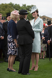 The Duchess of Cambridge talks to guests during a garden party at Buckingham Palace in London.