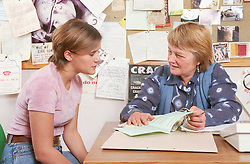 Teenage girl sitting at desk in office talking to female probation worker,