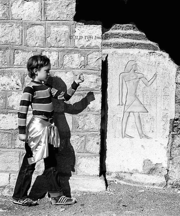 Boy with silver jacket wrapped around his loins imitates a Pharaonic pose at Saqqara.  Slightly beyond him is the Pharaonic relief he is imitating.