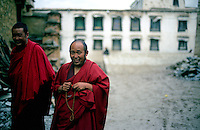 Monks wearing red robes smile as they walk through the monastery grounds in Lhasa, Tibet.