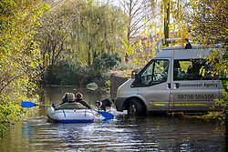 © Licensed to London News Pictures 16/11/2019, Cerney Wick, UK. Residents of Cerney Wick, near Cirecenster paddle down a flodded road in the village past an Environment Agency van in a blow up dinghy. Photo Credit : Stephen Shepherd/LNP