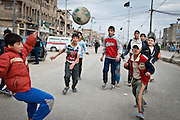 Children play soccer in the empty streets of Sadr City just before Friday prayers. The police, army, and local militia block streets all over Baghdad on Friday to prevent suicide bombers from attacking prayers.