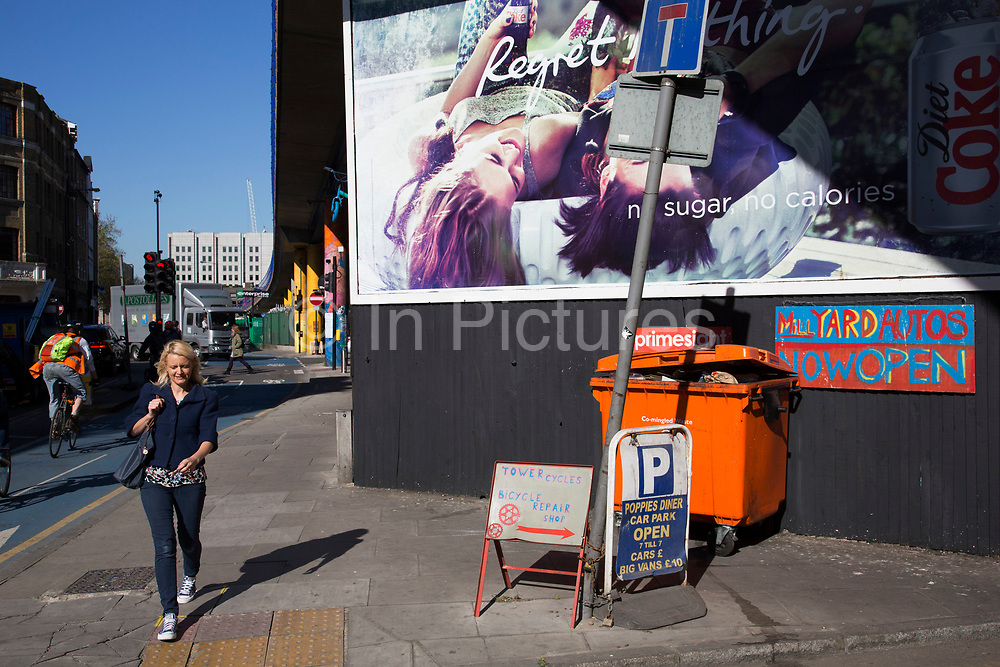 People passing an advertising billboard on a street corner on Cable Street, London, UK.