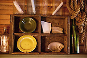 Old plates & pottery are displayed on a beat up wooden shelf