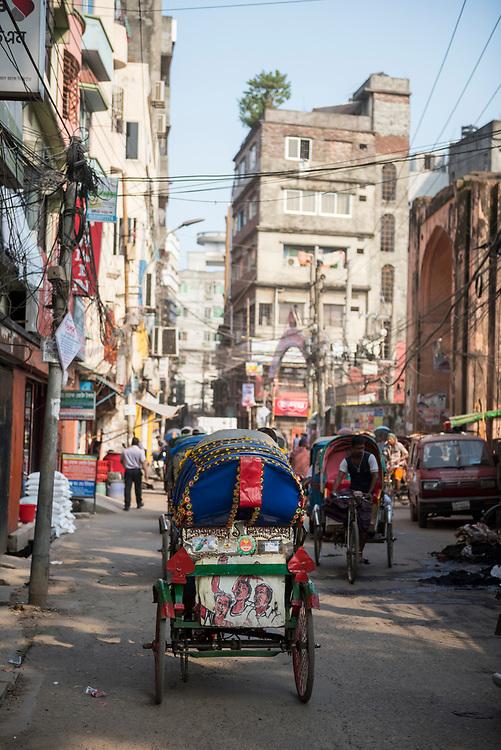 Dhaka, Bangladesh - November 1, 2017: Rickshaws navigate the crowded streets in the historic center of Dhaka.