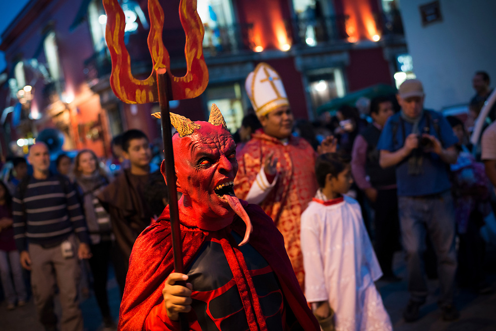 """A person wearing a devil costume walks down a street in the Mexican city of Oaxaca during Day of the Dead celebrations (""""Día de los Muertos"""" in Spanish)."""