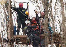 © Licensed to London News Pictures.  15/03/2015. Bristol, UK.  Specialist climbers from SGI Rescue cut a metal tube to which two women protesters are locked together, to remove protesters from trees on land owned by Bristol City Council. Campaigners are protesting against the Bristol Metrobus proposed bus-only bridge and junction on the M32 which will be on existing allotments and land which is grade one agricultural quality soil, and which the campaigners say should be preserved for growing food, especially as this year Bristol is the Green Capital of Europe 2015.  The Metrobus project is designed to save journey times and encourage more commuters out of cars and onto buses.  The protesters have been camped and in tree houses for 6 weeks.  Photo credit : Simon Chapman/LNP