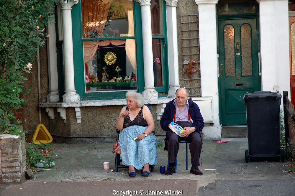 Proud and characterful older couple sitting on pavement outside their home.