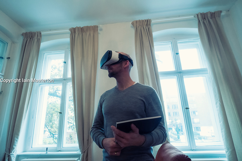 Real Estate agent in home wearing Virtual Reality (VR) goggles