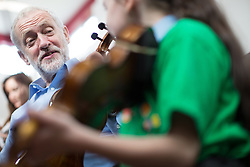 © Licensed to London News Pictures . 27/09/2016 . Liverpool , UK . Labour Party leader JEREMY CORBYN is shown how to play the violin by JESSICA KELLY (10) during a visit to Faith Primary School in Liverpool , where he listens to and then joins in with the school orchestra . Photo credit : Joel Goodman/LNP