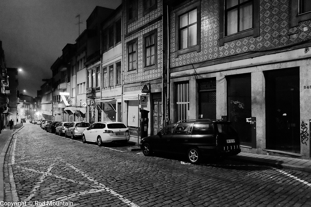 Porto, Portugal - February 13, 2018 - Walking along R. Do Bonjardim after dark in search of a restaurant. <br /> <br /> Image: © Rod Mountain<br /> <br /> https://www.rodmountain.com <br /> <br /> http://bit.ly/RM-archive<br /> <br /> http://bit.ly/Porto-BW<br /> <br /> http://bit.ly/Porto_PT<br /> <br /> Instagram<br /> @visitportugal <br /> <br /> FaceBook<br /> @visitportugal <br /> @visitporto.portal<br /> @TurismoPortoNortePortugal<br /> @TurismodePortugal<br /> <br /> Twitter<br /> @visitportugal <br /> <br /> Pinterest<br /> @visitportugal                                      #urbexeurope #europetravel #turismoemportugal #portugal🇵🇹 #urban #streetfinder #streetmagazine #moodygrams #1stinstinct #documentaryphotography #photographylover #nights #nightout #hotelstay #TravelAwesome #thestreetcollective #bnw_globe #blackandwhiteisworththefight  #bnw_demand #bnw_captures #bnwlife #latergram