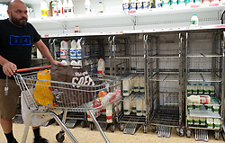 © Licensed to London News Pictures. 31/07/2021. London, UK. A shopper walks past nearly-empty shelves of milk in Sainsbury's, north London. The UK's biggest milk processor, Arla Foods UK, has said that about 600 individual stores out of the 2,400 that it routinely supplies missed a delivery due to the pingdemic and a lack of lorry drivers. The pingdemic has seen staff shortages at supermarkets, resulting in less stock making its way to supermarket shelves. Photo credit: Dinendra Haria/LNP