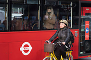 Young woman on a bus looks closely at her smart phone while a cyclist passes by outside as the national coronavirus lockdown three continues on 5th March 2021 in London, United Kingdom. Public transport use is still low amongst the public, with all transport for London services aiming to limit numbers. With the roadmap for coming out of the lockdown has been laid out, this nationwide lockdown continues to advise all citizens to follow the message to stay at home, protect the NHS and save lives, and the streets of the capital are quiet and empty of normal numbers of people.