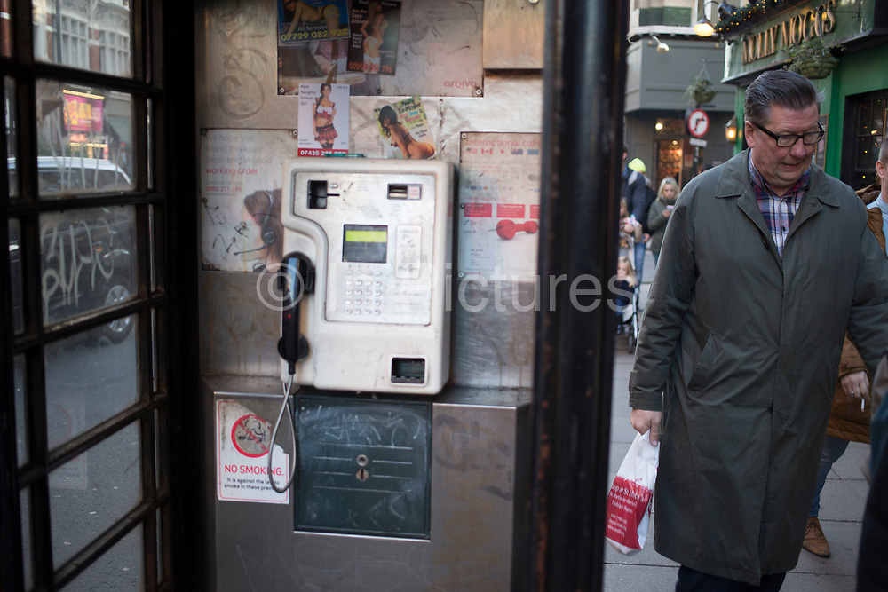 People passing a public telephone box which has sex cards tacked up inside. These advertising cards for prostitutes are how (mainly) girls or women advertise for sexual services under the guise of other 'services' like massage for example.