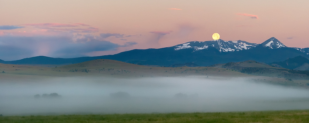 The moon sets over the Tabacco Root Mountains as some mist lifts off a field near the Madison River.