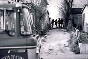Fire truck parked outside alley in Fulton Mo., 1973. Fireman's silhouettes far in the alley. Black & White from film.