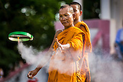 28 JUNE 2014 - DAN SAI, LOEI, THAILAND: A Buddhist monk at Wat Ponchai launches a small rocket powered flying disc during the Ghost Festival in Dan Sai. Phi Ta Khon (also spelled Pee Ta Khon) is the Ghost Festival. Over three days, the town's residents invite protection from Phra U-pakut, the spirit that lives in the Mun River, which runs through Dan Sai. People in the town and surrounding villages wear costumes made of patchwork and ornate masks and are thought be ghosts who were awoken from the dead when Vessantra Jataka (one of the Buddhas) came out of the forest.    PHOTO BY JACK KURTZ