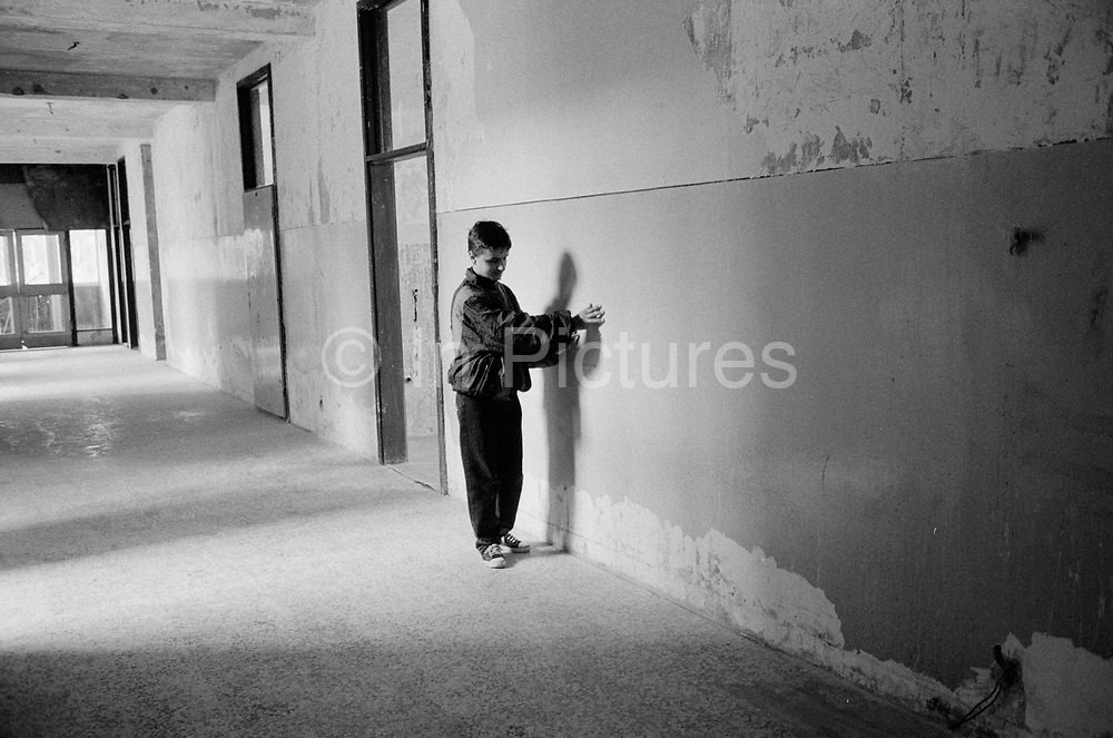 A boy makes his way to class in the destroyed  Blind School.The Blind School Sarajevo, is the only centre in Bosnia for children and young adults. It was extensively damaged during the civil war an was used by the Bosnian Serb army as a military position from which to snipe and shell the city. The few teaching staff left during the war managed to visit some of their blind pupils and continue a limited education. The school reopened after the war ended but conditions remain dire.