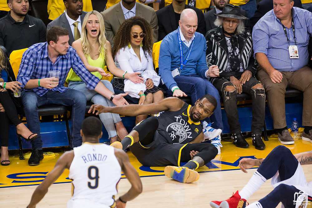 Golden State Warriors forward Kevin Durant (35) crashed into fans during Game 2 of the Western Semifinals against the New Orleans Pelicans at Oracle Arena in Oakland, California, on May 1, 2018. (Stan Olszewski/Special to S.F. Examiner)