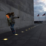 WASHINGTON, DC - DECEMBER 18: Ada Burk, 8, of Lubbock, TX, jumps between the spotlights at the base of the Washington Monument in Washington, DC, on December 18, 2020. The monument is now closed as a precaution after Interior Secretary David Bernhardt — who gave a private, nighttime tour to other Trump appointees this week — tested positive for the coronavirus. (Photo by Craig Hudson for The Washington Post)