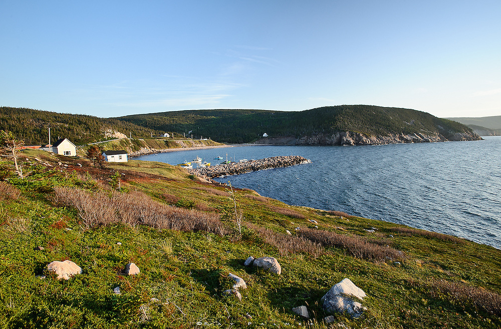 White Point, Cape Breton, Canada<br /> In the late evening, the weakening light raked across the grass and intensified the greens of the meadow atop the cliffs that dropped off the point.  A dirt track led up here to about the high ground,  then descended down to land's end, broken in pieces and split by the sea.  The random houses of the community are tucked back over the hill and spread out around the cove, sturdy structures strategically out of the elements.  It must be a welcome place, over that hill or around the breakwall when you need to get out of the elements.  And if the elements include an escape from the pressures of living a hectic life, there's shelter from that here, too.