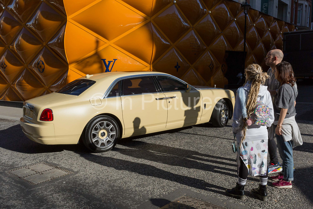 A Rolls-Royce limousine drives past less wealthy onlookers opposite the temporary renovation hoarding of luxury brand Louis Vuitton in New Bond Street, on 25th February 2019, in London, England.