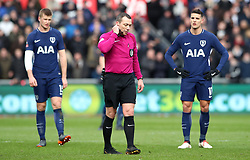 Referee Kevin Friend (centre) waits for the Video Assistant Referee (VAR) system to rule if the goal from Tottenham Hotspur's Son Heung-Min (not in shot) is ruled offside during the Emirates FA Cup, quarter final match at the Liberty Stadium, Swansea.