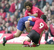 Cardiff, Wales, 7th March 2004, Six Nations International Rugby, Wales vs France, Millennium Stadium,  [Mandatory Credit; Peter Spurrier/Intersport Images], Six Nations Rugby - Wales v France<br /> Wales skipper Colin Charvis [carring a nose injury] helps Gareth Cooper, stop the charging French attacker.<br /> <br /> <br />    [Mandatory Credit, Peter Spurrier/ Intersport Images]