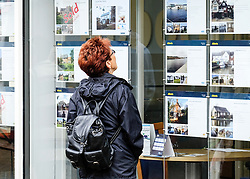 A woman looking in an estate agents window.
