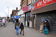 Local response to Coronavirus is felt on a street by street level as People wearing face masks go about their day to day shopping on Kings Heath High Street on 6th April 2020 in Birmingham, England, United Kingdom. Coronavirus or Covid-19 is a new respiratory illness that has not previously been seen in humans. While much or Europe has been placed into lockdown, the UK government has announced more stringent rules as part of their long term strategy, and in particular social distancing.
