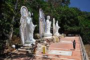 Woman tourist filming three statues--two of Bodhisattvas (Pho Hien Bo Tat on left, Quan'Am on far right), and A Di Da, or Amitabha, the Buddha of the past, in the centre. Ta Cu mountain, Binh Thuan Province, Vietnam