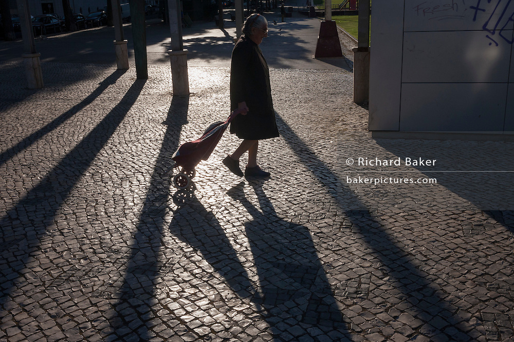 An elderly lady tows her shopping trolley behind her, as the passes sunlight and shadows at Alameda metro station, Lisbon, Portugal.