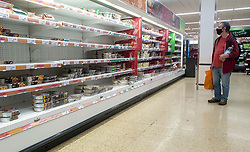 © Licensed to London News Pictures. 08/10/2021. London, UK. A shopper looks at nearly empty shelves of pre-cooked meat products in Sainsbury's, north London. The Government and retailers warn that food and fuel shortages could continue until Christmas due to labour shortages following Brexit. Photo credit: Dinendra Haria/LNP