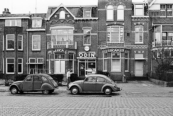 Nederland, Nijmegen, 10-10-1980Serie beelden over het wonen en sociale woningbouw in verschillende wijken van de stad.In het kader van stadsvernieuwing en renovatie van buurten gemaakt. Importeur van het duitse kwaliteitsmerk Leitz, Leica, apparatuur voor fotografie en medische microscopen ODIN aan de Graafseweg. Een citrien 2cv, lelijke eend, en een volkswagen kever, vw, staan geparkeerd. Beide iconen van de autoindustrie uit resp. frankrijk en duitsland. autobezit voor de gewone man, burger.FOTO: FLIP FRANSSEN/ HH