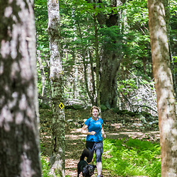 A woman trail running with her dog at the Shepards Farms Preserve in Norway, Maine.