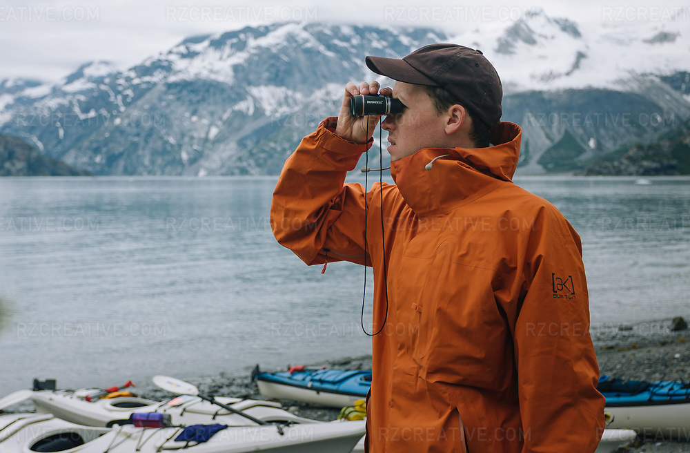 A man looks through a pair of binoculars in Alaska's Glacier Bay National Park and Preserve. Photo © Robert Zaleski / rzcreative.com<br /> —<br /> To license this image contact: robert@rzcreative.com