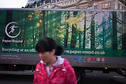 Chinese woman in front of recycling lorry with green forest and nature theme.
