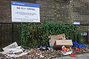 Fly-tipping left on a Lewisham street beneath a council sign threatening fines ad/or imprisonment. cardboard boxes, childrens' toys and plastic can be seen on the ground under the sign - a blatant disregard for local bylaws and rules against the dumping of refuse and garbage. Enforcement officers operate in this area and they have the power to enforce penalties of up to £50,000 and/or six months imprisonment - a threat but obviously not enough of a deterent.