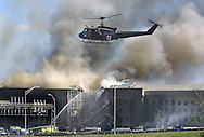 A 12.2 MG IMAGE OF:.PENTAGON 911. An Army medivac helicopter  takes off from the Pentagon parking lot with the burning Pentagon in background Photo by Dennis Brack.